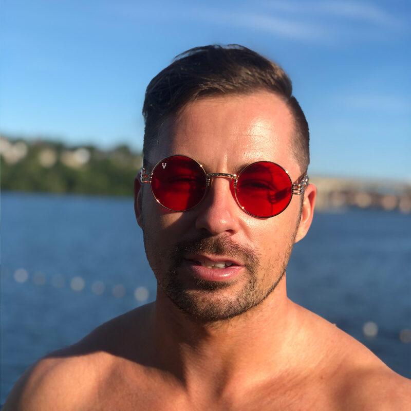 Solglasögon med rött genomskinligt glas och guld båge